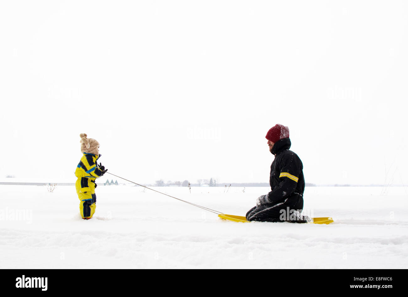 Son pulling father on sledge (2-3 years) Stock Photo
