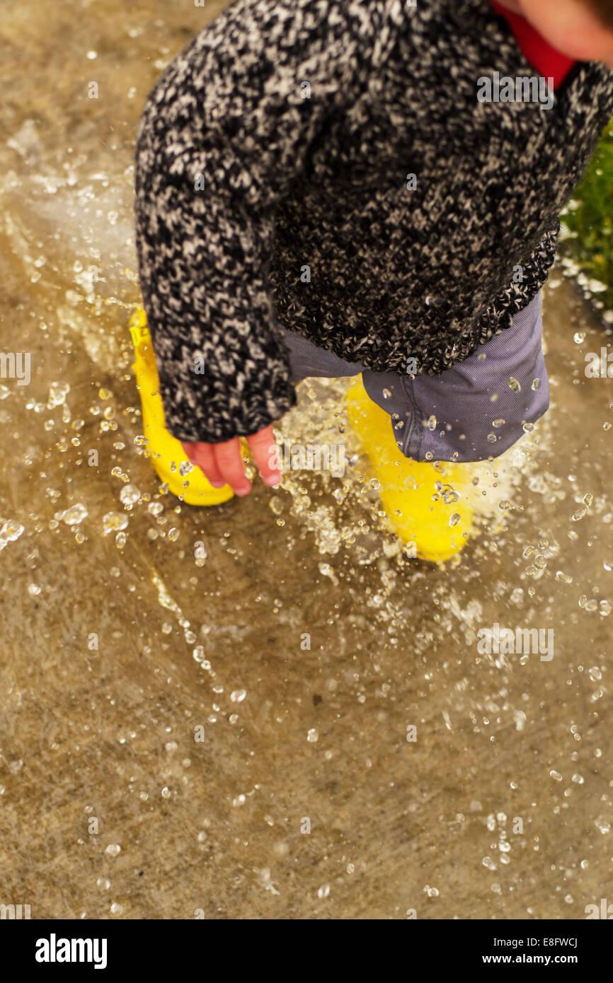 Boy walking through puddle (2-3 years) Stock Photo