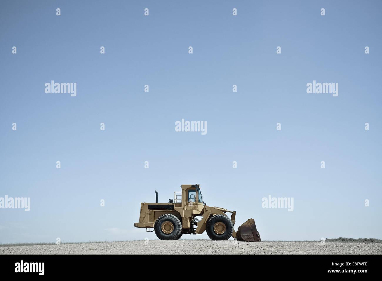 USA, Wyoming, Bulldozer against blue sky - Stock Image