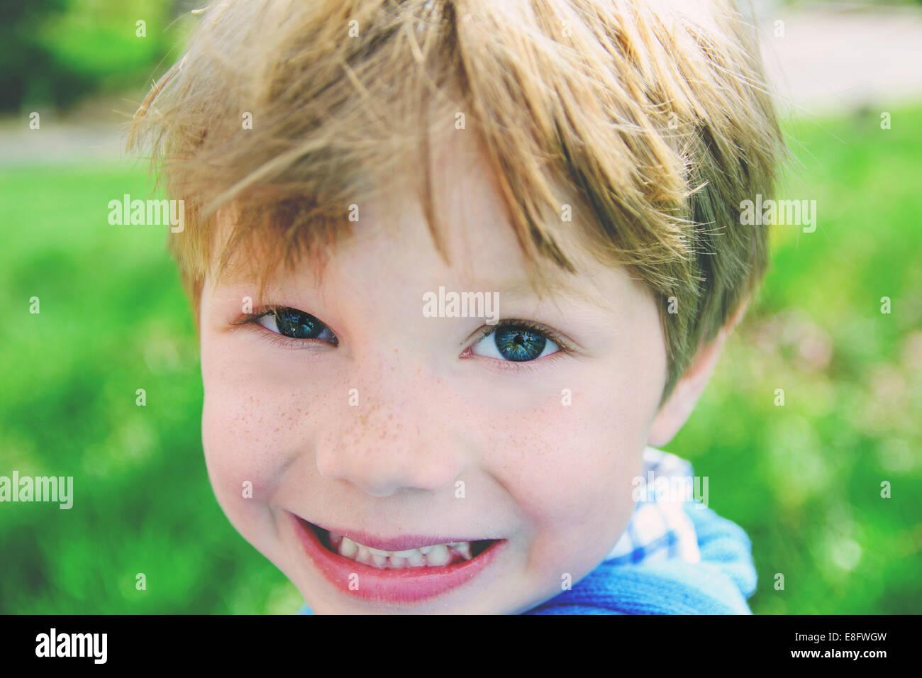 Boy (4-5) smiling at camera - Stock Image