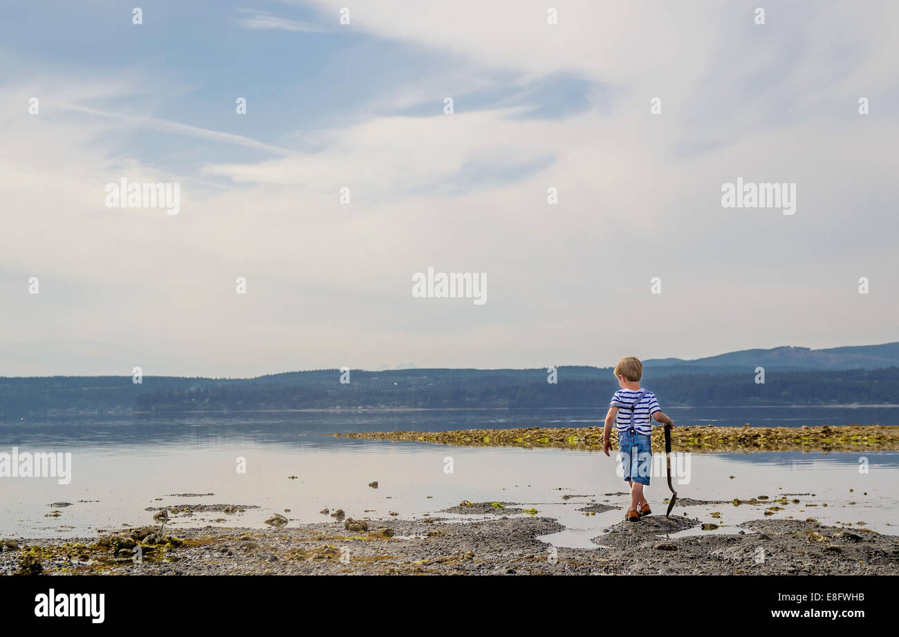 Boy (4-5) walking along lake - Stock Image