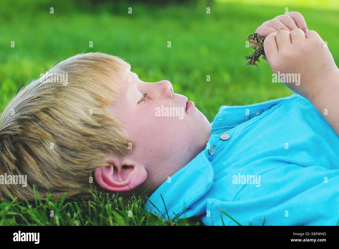 Boy (4-5) looking at frog - Stock Image
