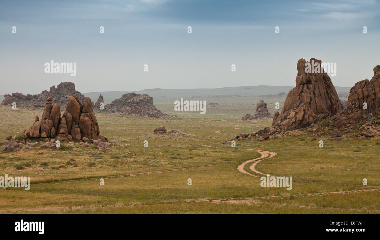 Dirt track between rock formations in field - Stock Image