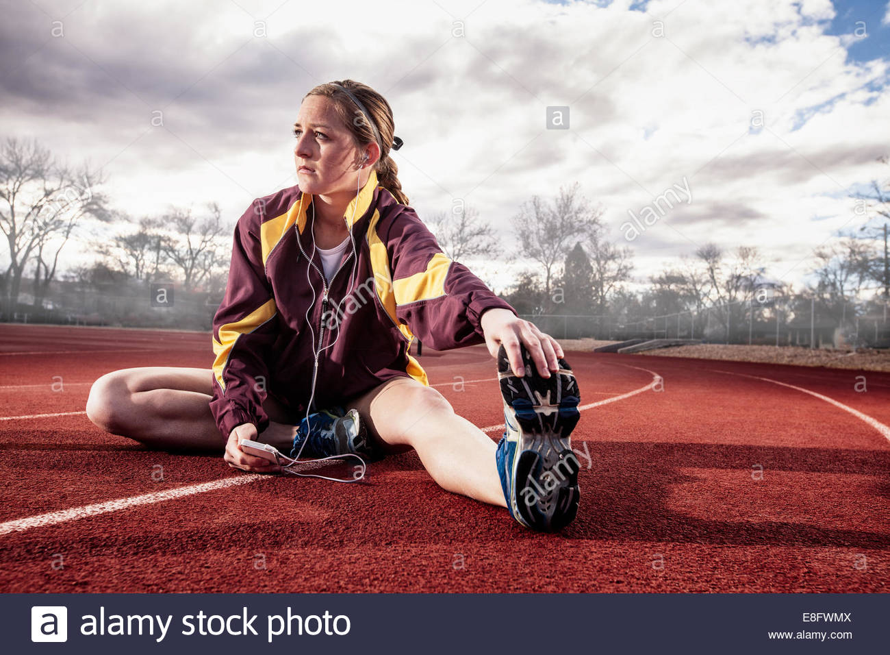 Young woman sitting on running track stretching while listening to music - Stock Image