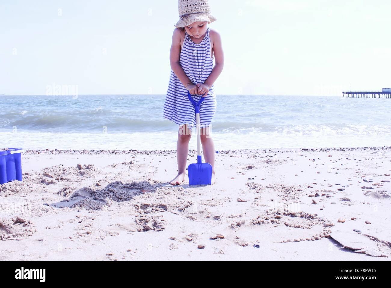 Girl digging on the beach - Stock Image