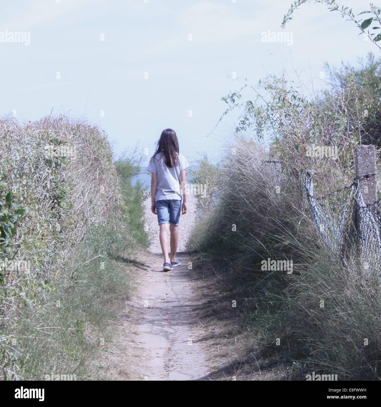 Rear view of girl walking along footpath - Stock Image