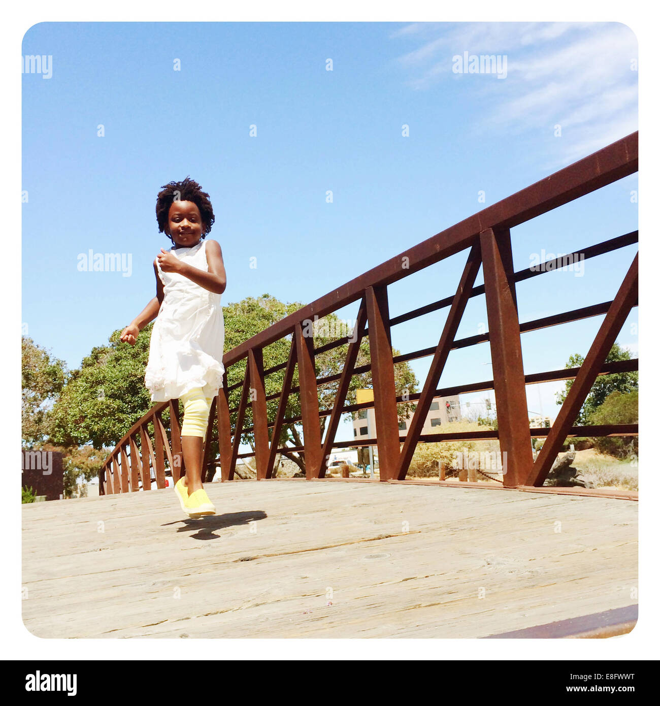 Girl running across bridge - Stock Image