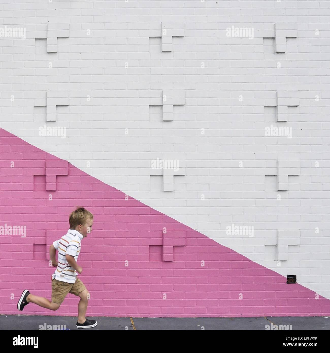 Boy running past pink and white wall - Stock Image