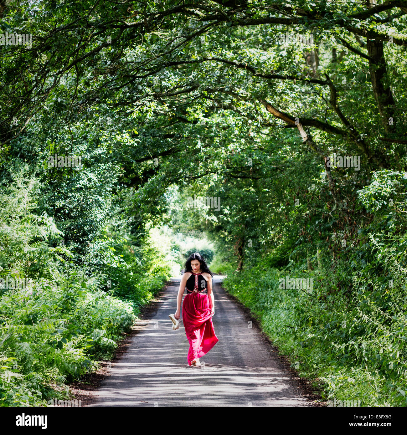 UK, England, Berkshire, Women in dress walking down country lane - Stock Image