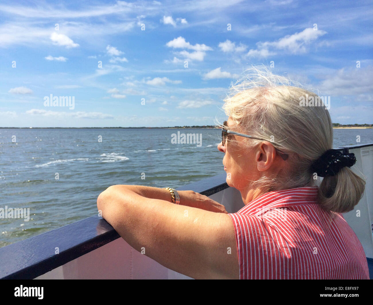 Senior woman on boat looking out to sea - Stock Image