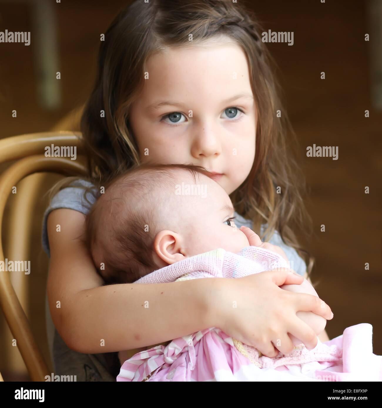 Girl (4-5 years) cuddling baby sister - Stock Image