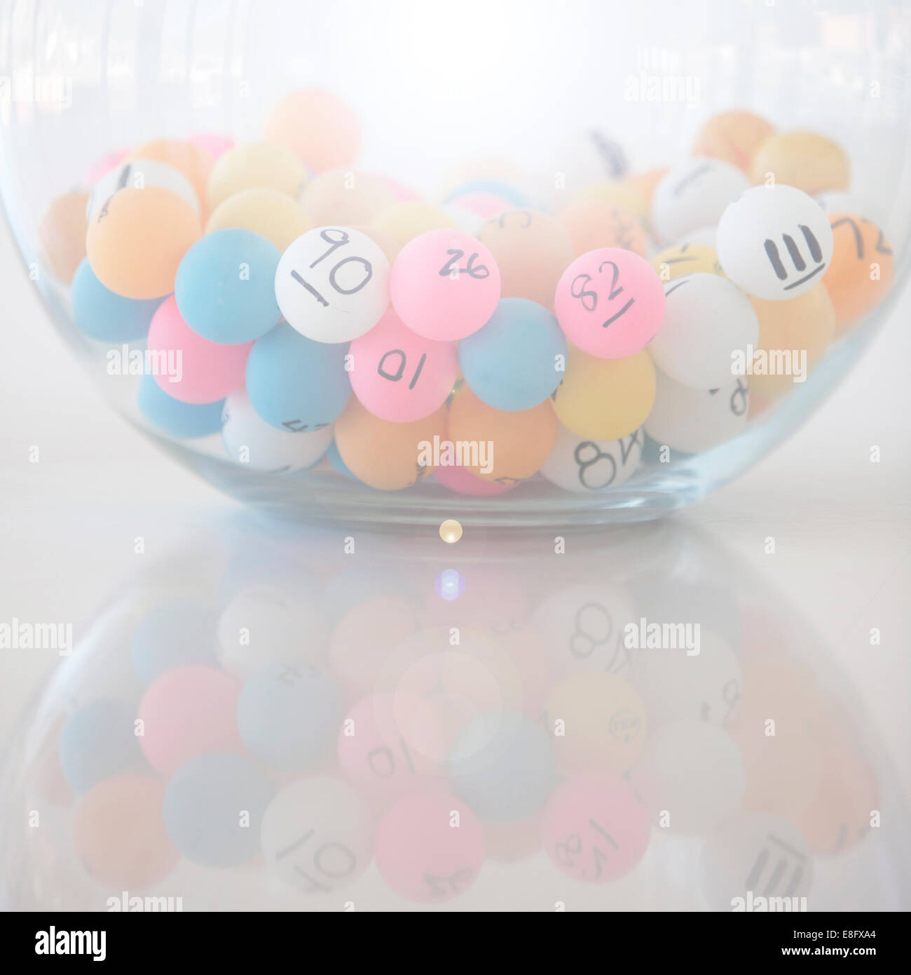Multi-colored Lottery balls in glass bowl - Stock Image