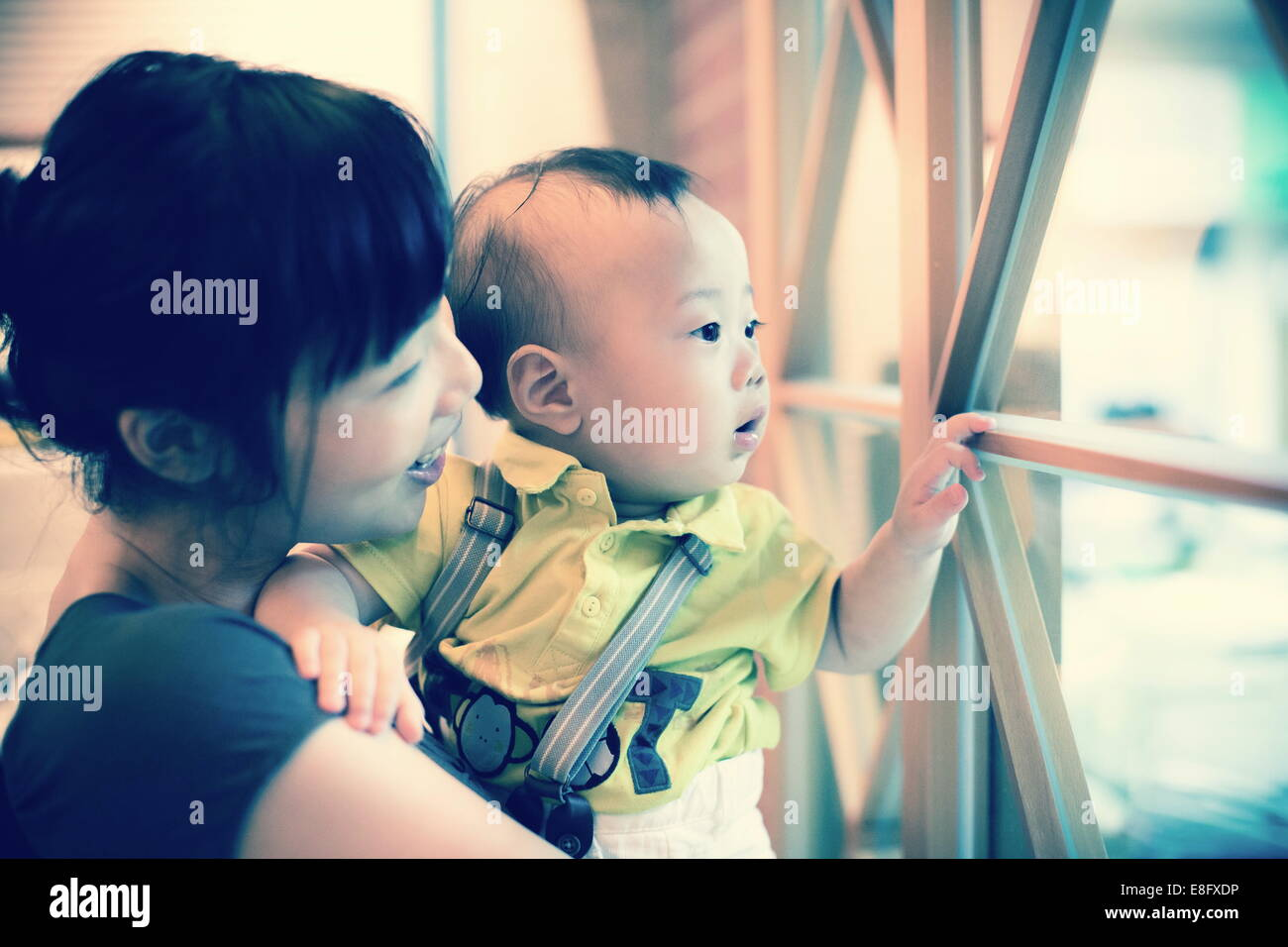 Curious child looking through window - Stock Image