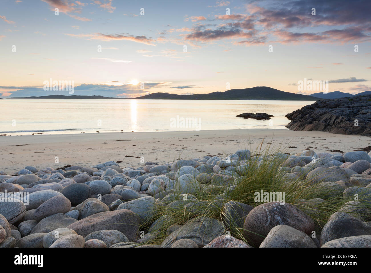 Seilebost beach boulders and sunset over Taransay, Isle of Harris, Outer Hebrides, Scotland - Stock Image