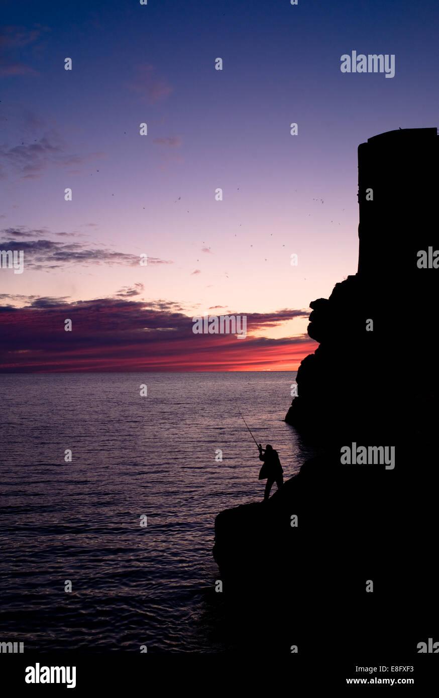 Croatia, Dubrovnik-Neretva, Dubrovnik, Silhouette of man fishing from rock formation - Stock Image