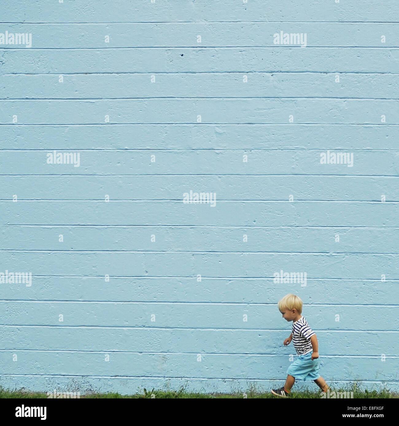Boy walking past a blue wall - Stock Image