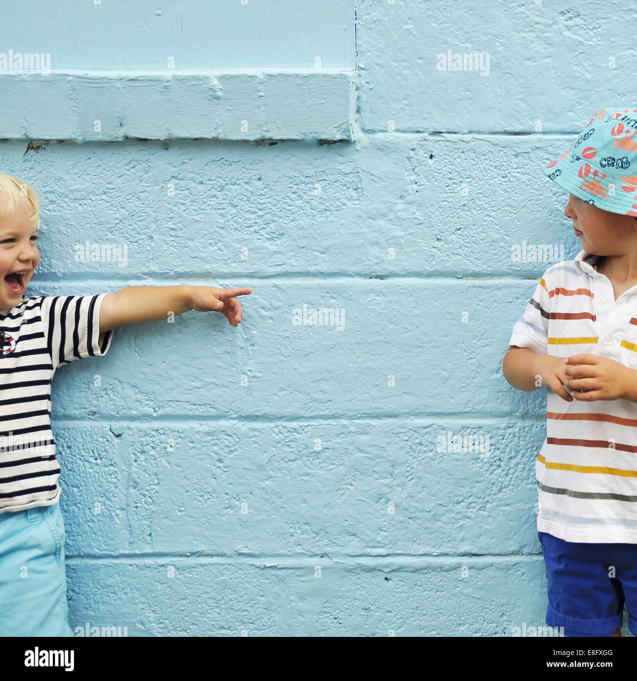 Two boys messing about in front of a blue wall - Stock Image