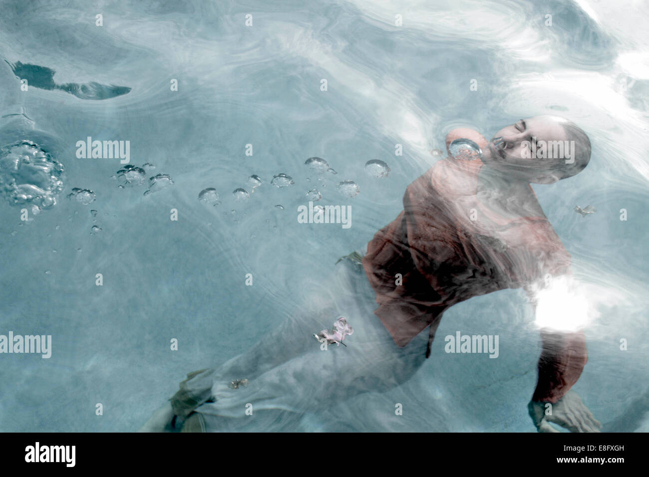 Fully clothed woman swimming underwater - Stock Image