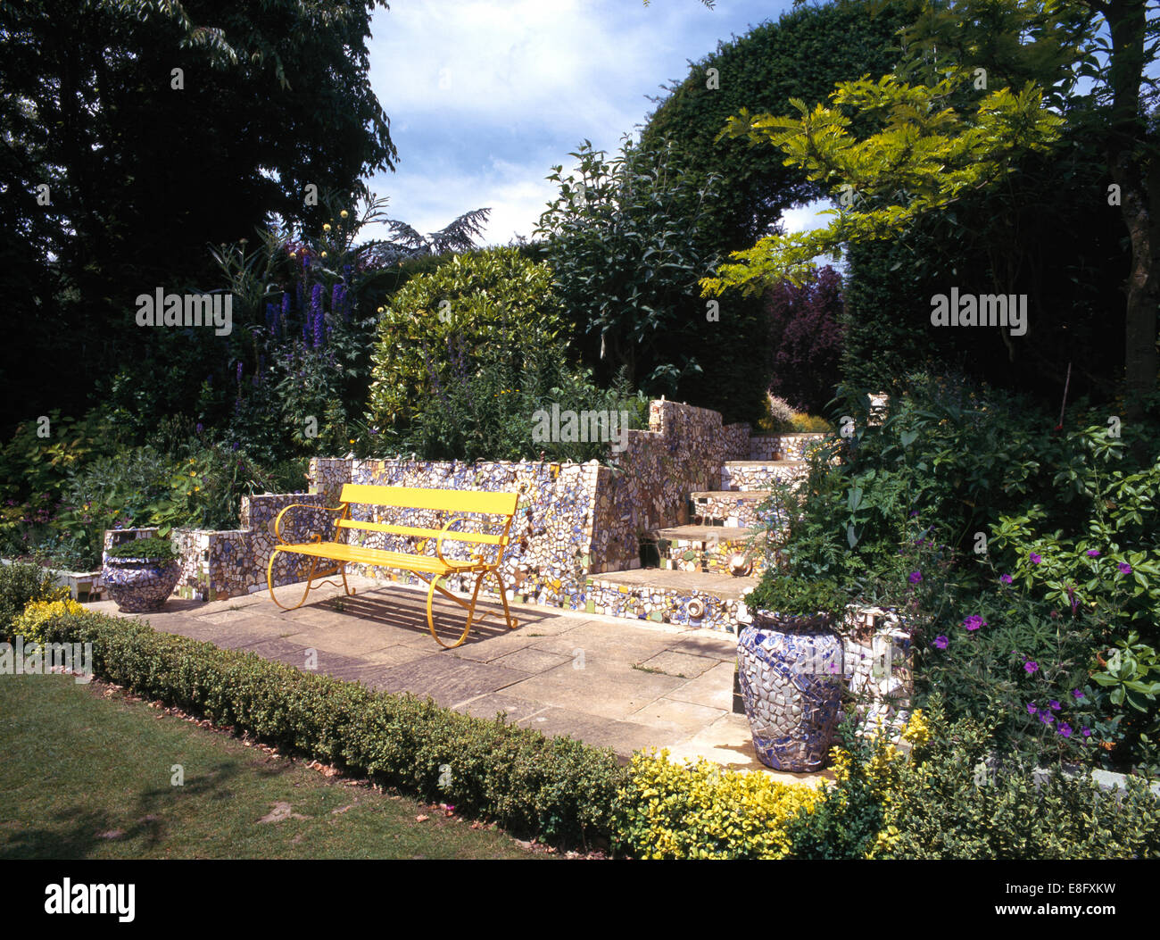 Yellow painted bench on patio edged with low clipped hedging in large country garden - Stock Image