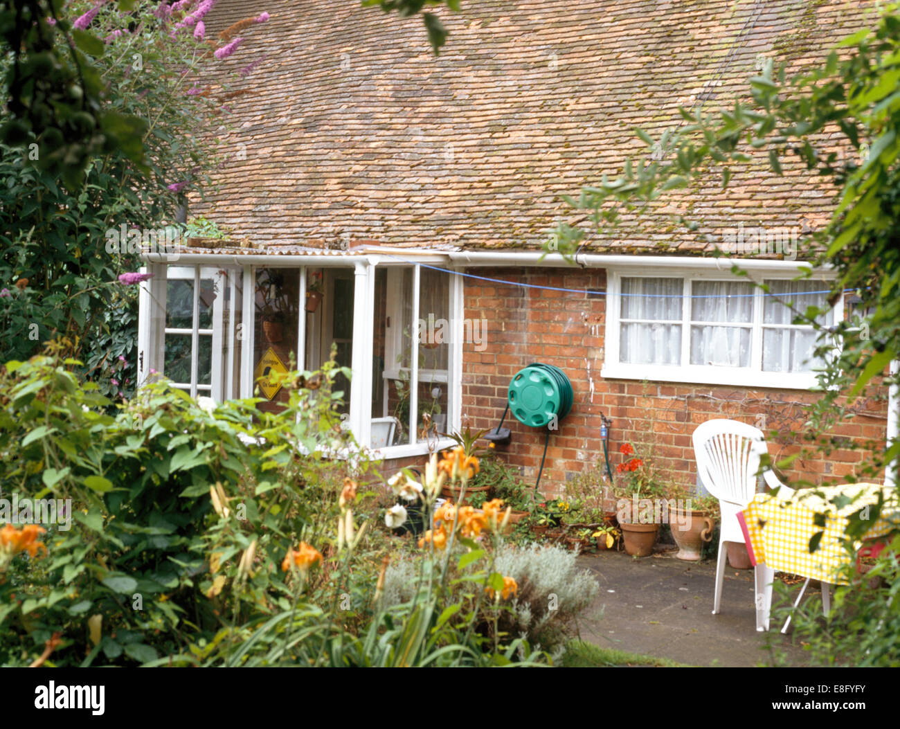 Hose Reel On Wall Of Brick Cottage With Small Conservatory Style Glass  Porch And Paved Patio