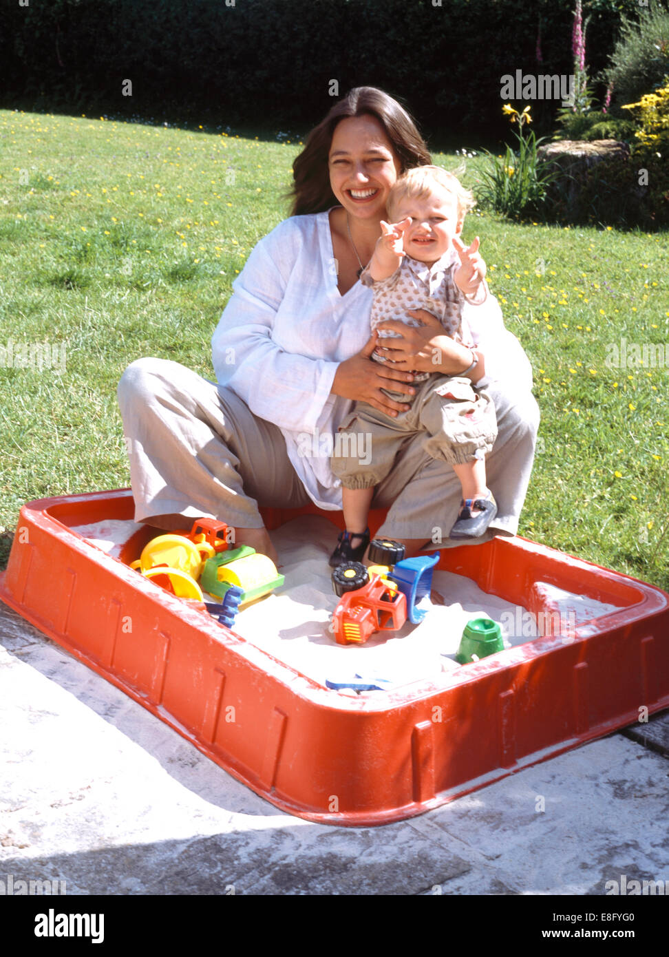 Portrait of a young mother and toddler sitting in a sandbox - Stock Image