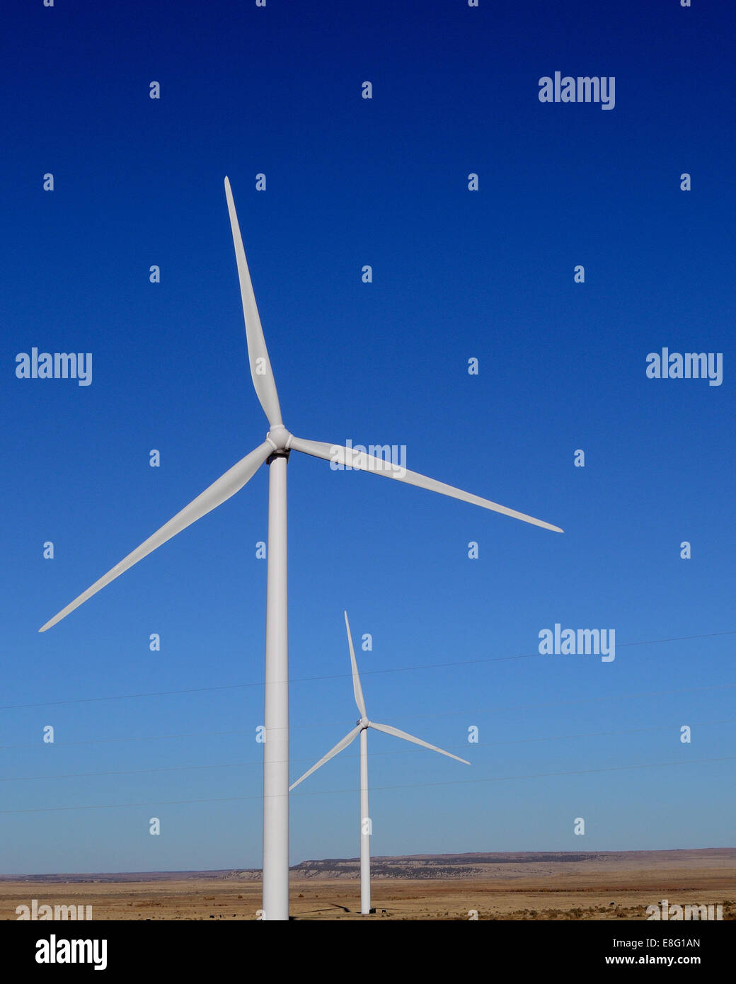 Two wind-powered turbines operating in-sync. - Stock Image