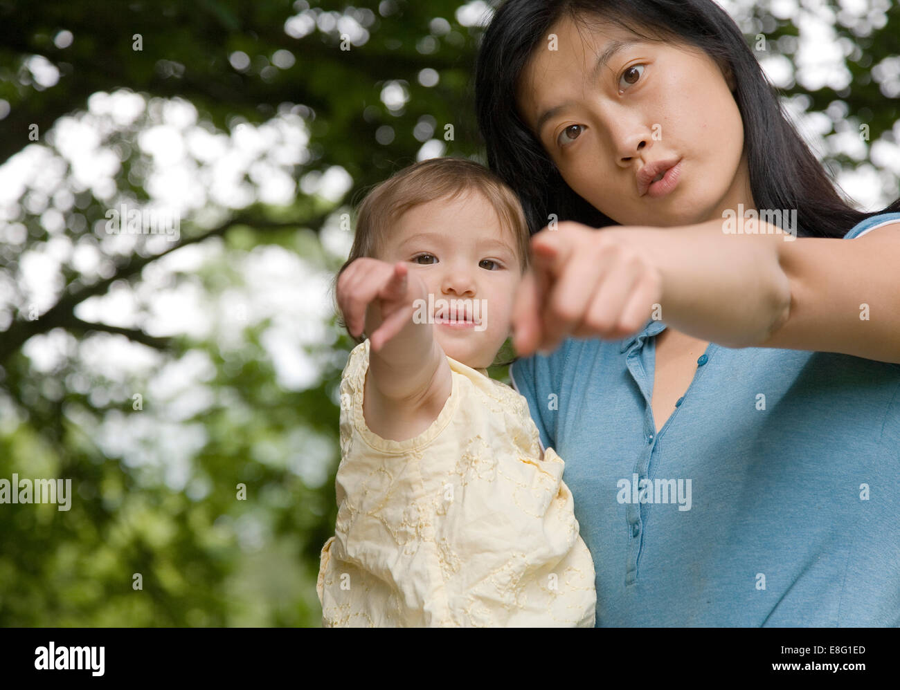 a mixed ethnicity (East Asian / caucasian) female toddler being held in the arm of her Korean East Asian mother, - Stock Image