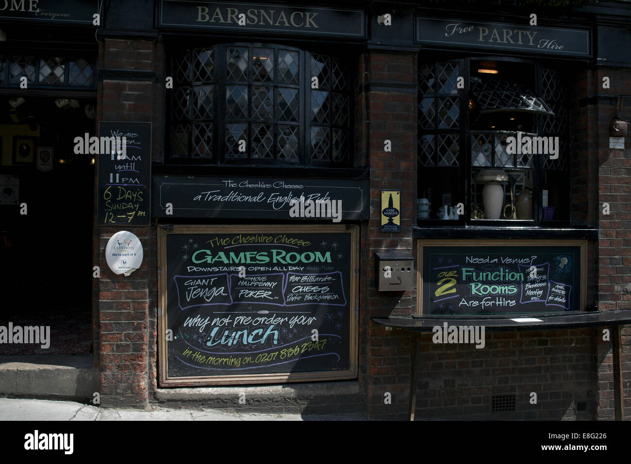 Exterior pub public house London England signs saying games function room lunch menu sunny day - Stock Image