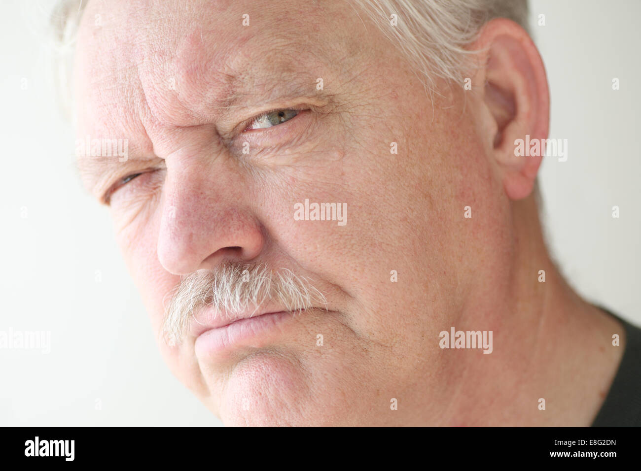 Senior man with a suspicious or skeptical expression - Stock Image