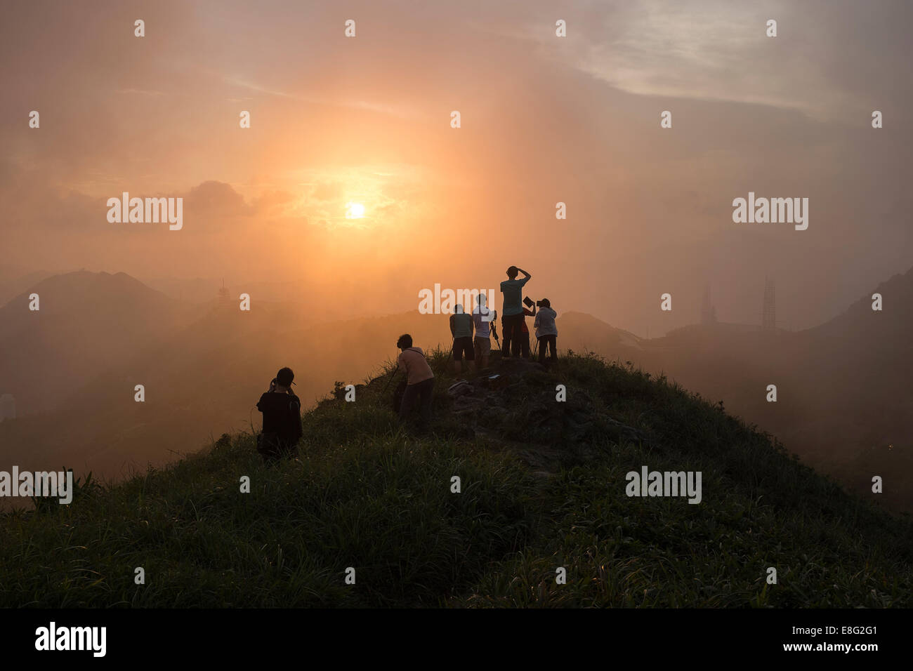 Photographers shoot the setting sun from the top of Kowloon Peak (Fei Gno Shan) in Hong Kong on August 30, 2014 Stock Photo