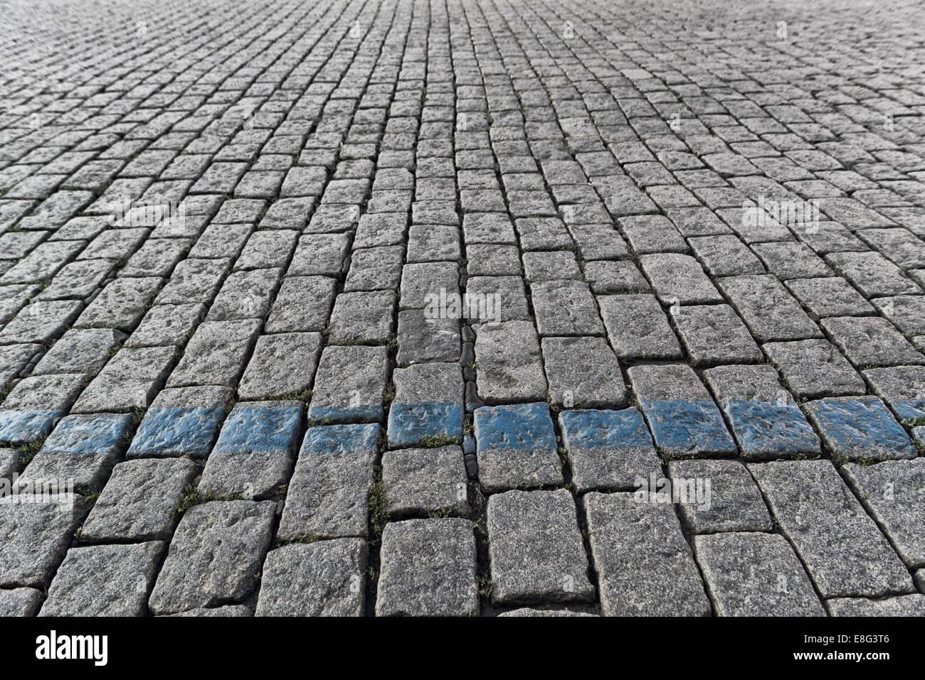Cobblestone pavement pattern vanishing in street perspective - Stock Image
