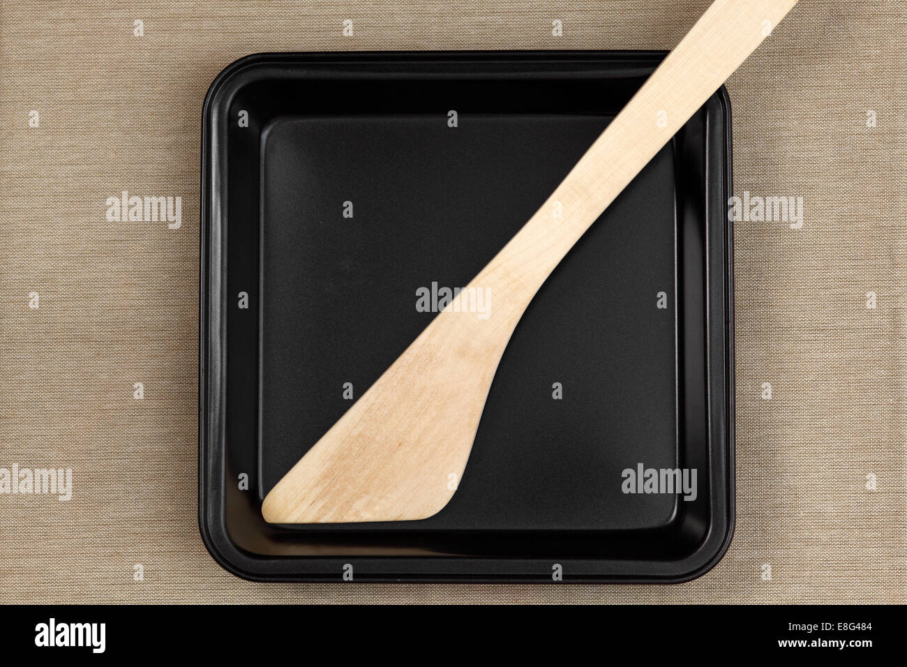 Baking sheet with Wooden Spatula on canvas background - Stock Image
