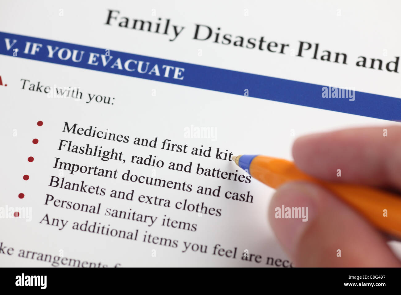 Family Disaster Plan and hand with ballpoint pen. Close-up. - Stock Image