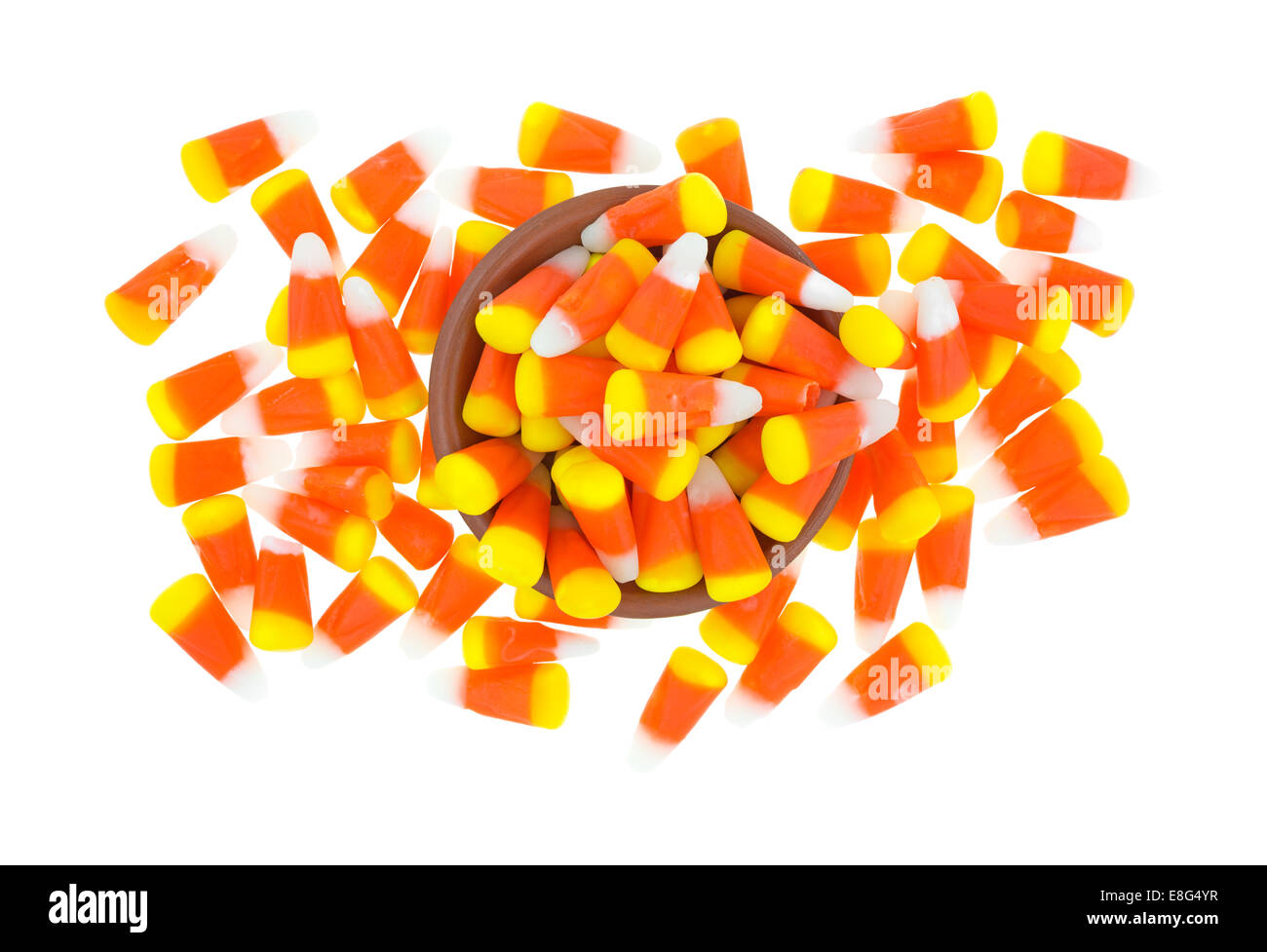 A mess of Halloween candy corn kernels on a white background with a small bowl in the center. - Stock Image