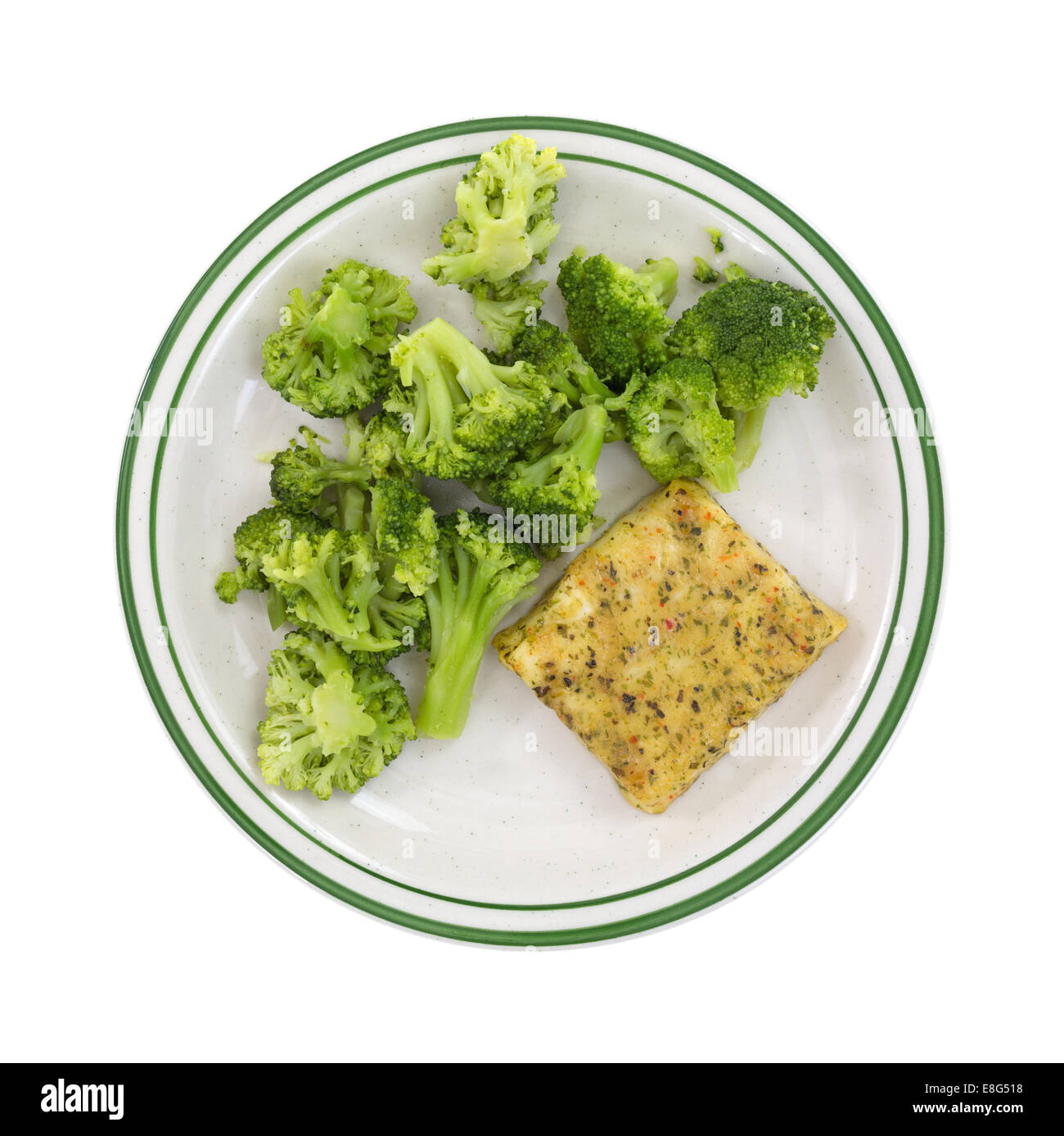 Top view of a meal of baked pollack with broccoli on plate against a white background. - Stock Image