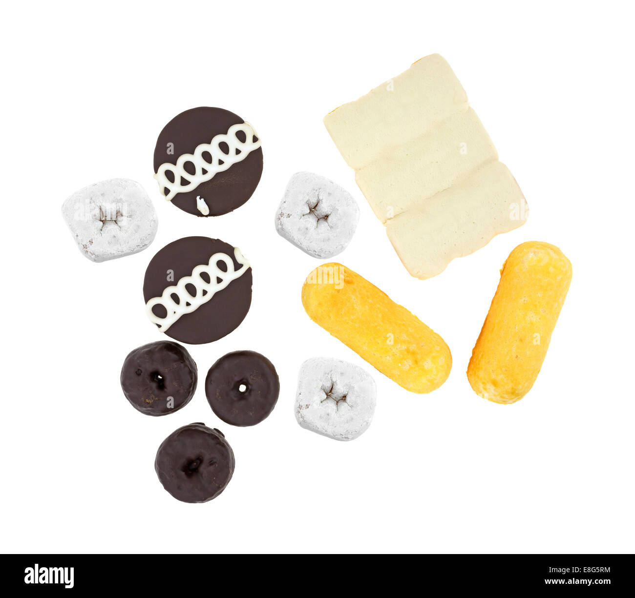 Several varieties of junk food cakes and donuts on a white background. - Stock Image