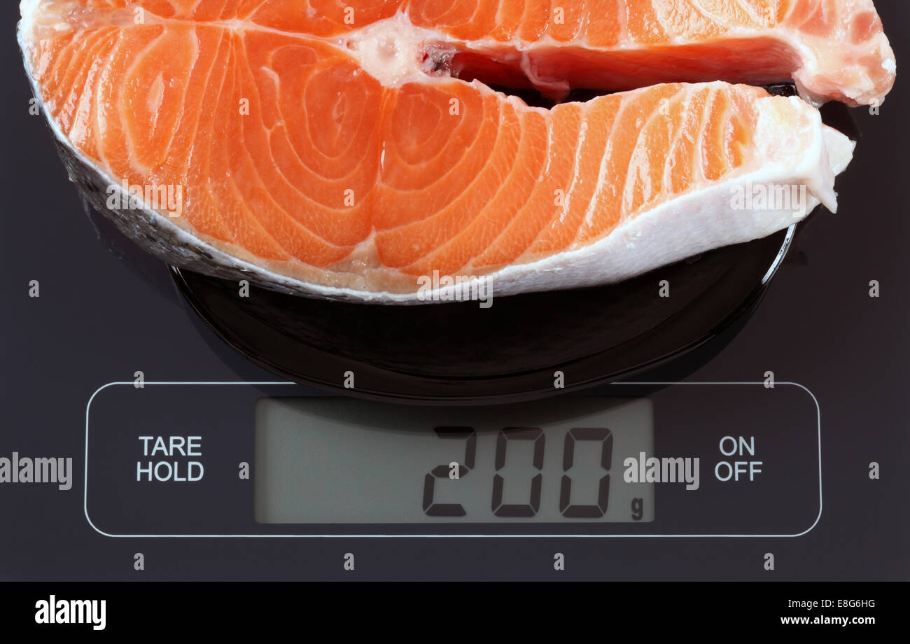 Steak of salmon fish in a black plate on digital scale displaying 200 gram. - Stock Image