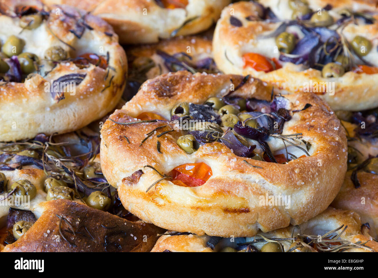 Focaccia, artisan bread, Italian flatbread with herbs, olives and tomatoes. - Stock Image