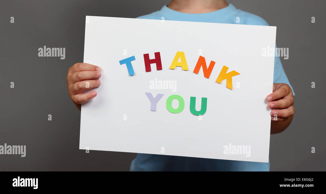 'Thank You' sign in children's hands. Letters cut from paper and pasted on sheet. - Stock Image