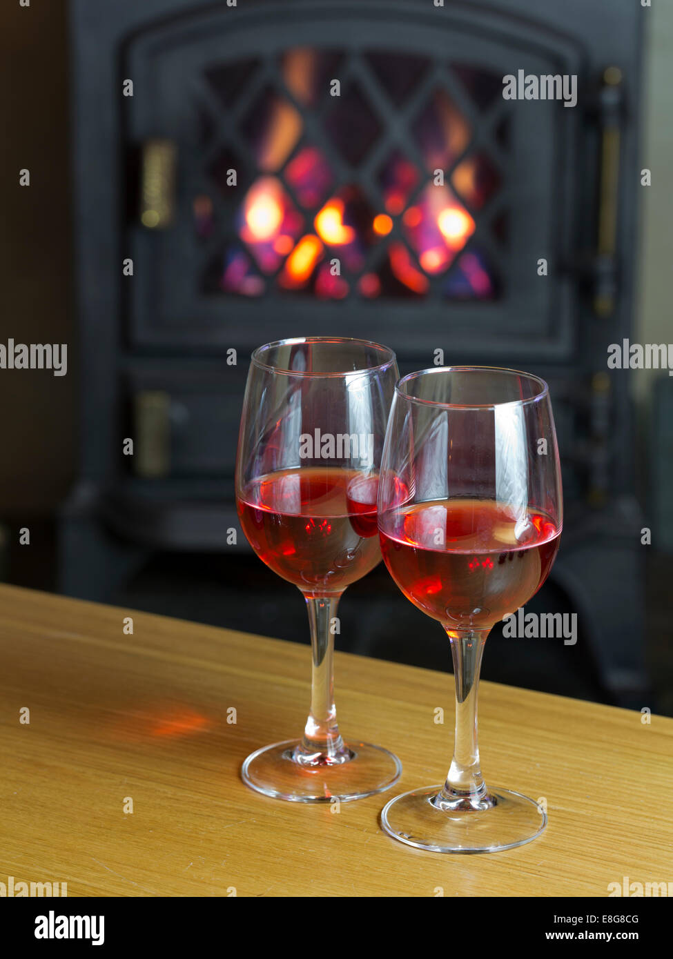 Two glasses of Sloe Gin on a wooden coffee table in front of a cast iron gas stove - Stock Image