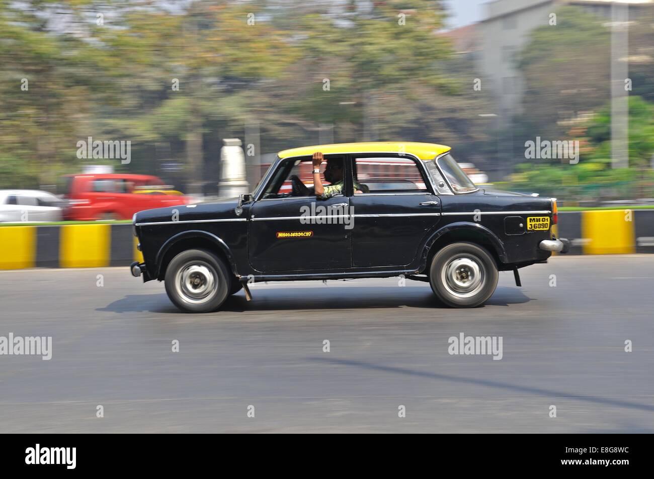 A Hindustan Ambassador Taxi driving along a city street in Mumbai, India - Stock Image
