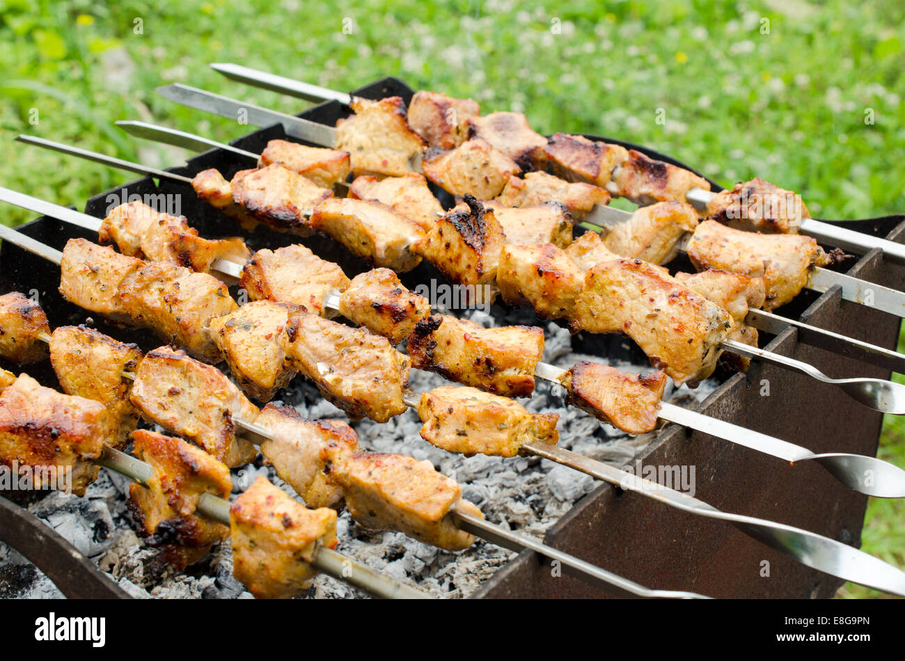 skewers of fried chicken on the grill - Stock Image