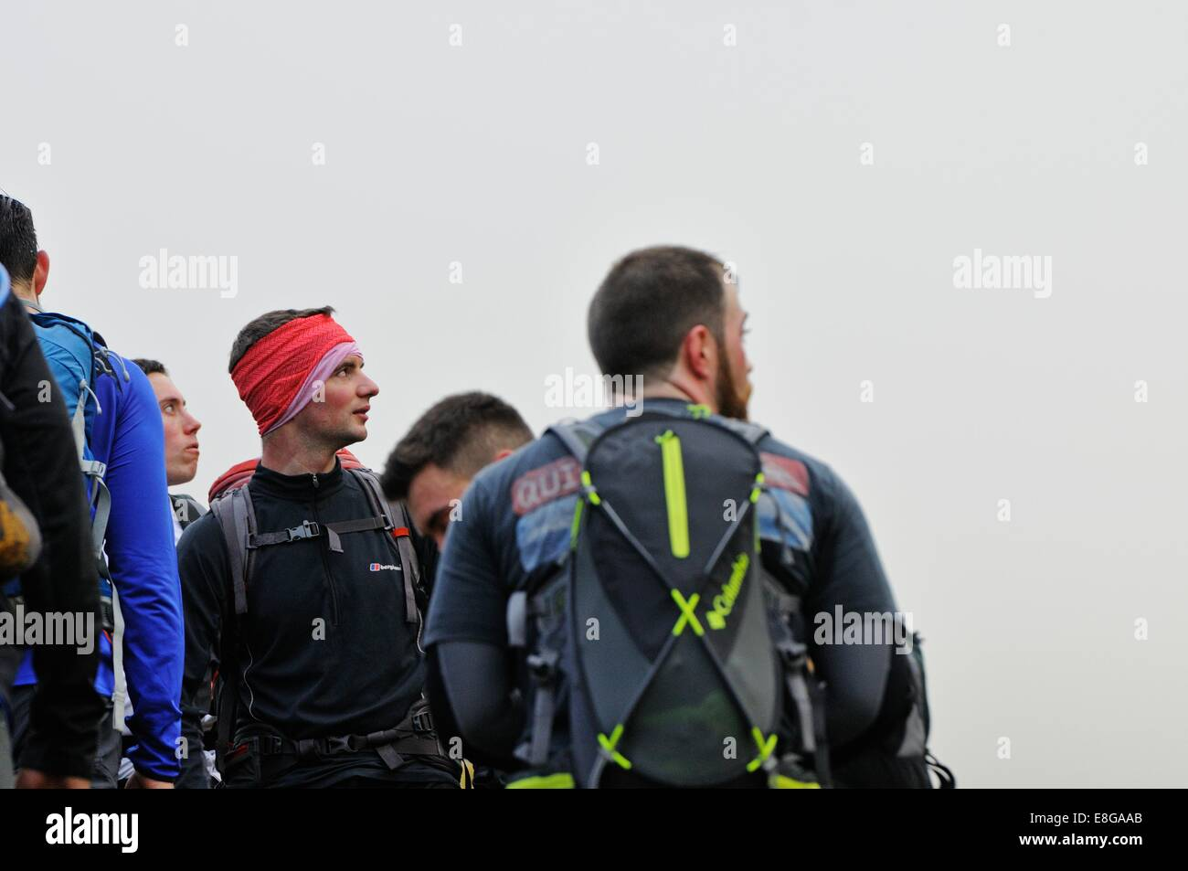Climbers from a Royal Navy team look up through the mist to towards the peak of Scafell Pike - Stock Image