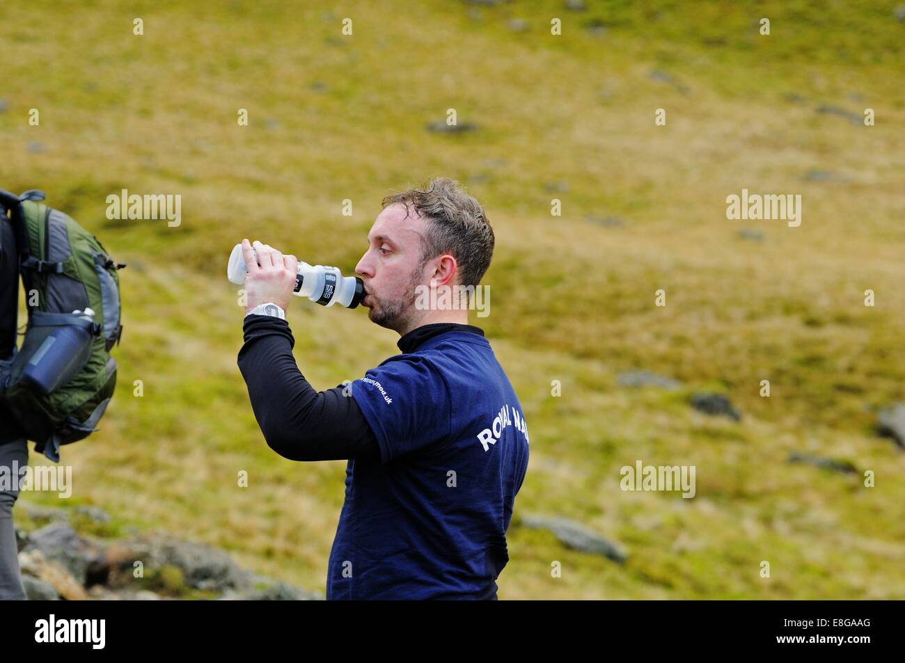 Fell Runner drinking from a water bottle on a trek up Scafell Pike in the Lake District - Stock Image