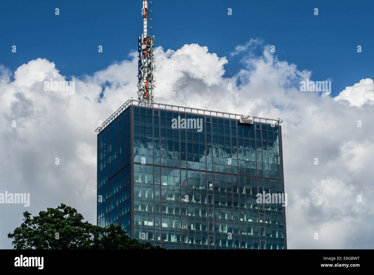 Modern glass building, with huge radio antena in Belgrade. Dramatic skies contribute to more intense , business - Stock Image