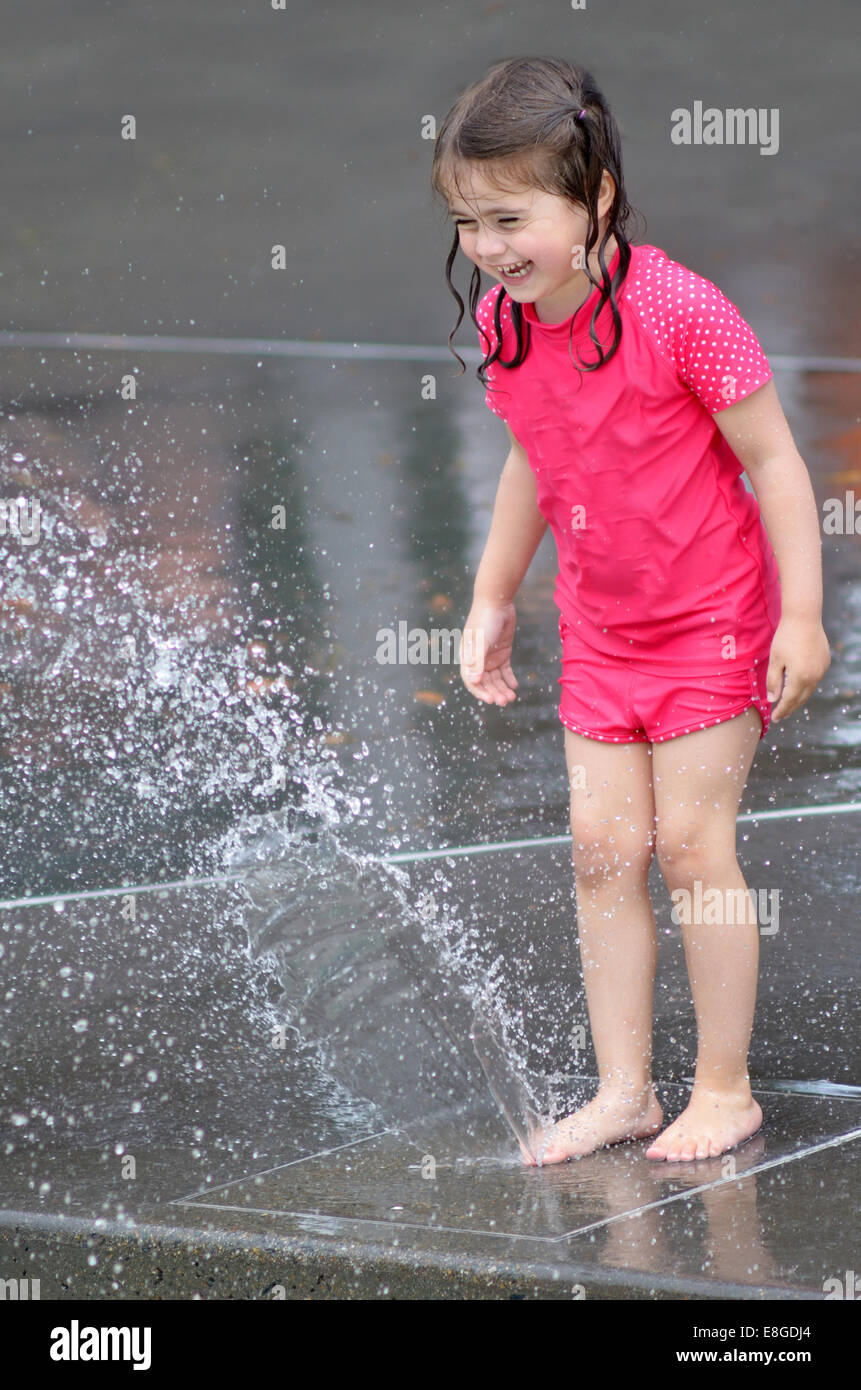 Child (girl age 04)  play water with water fountain. concept photo hot weather and heatwave. copyspace Stock Photo