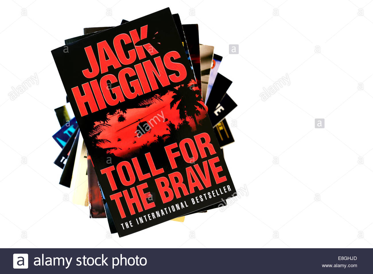 Jack Higgins book title Toll For The Brave, stacked used books, England - Stock Image