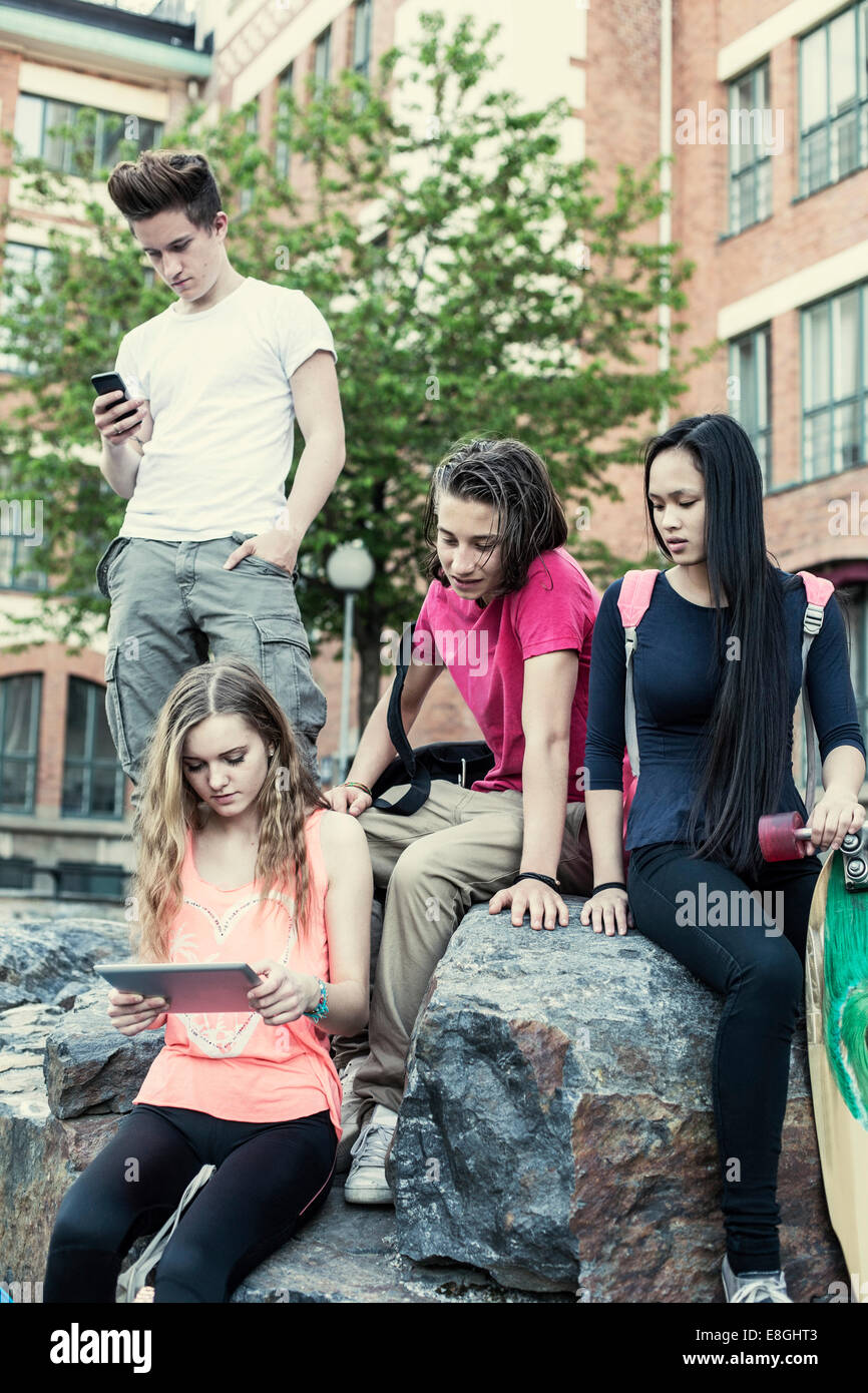 High school students using technologies at schoolyard - Stock Image
