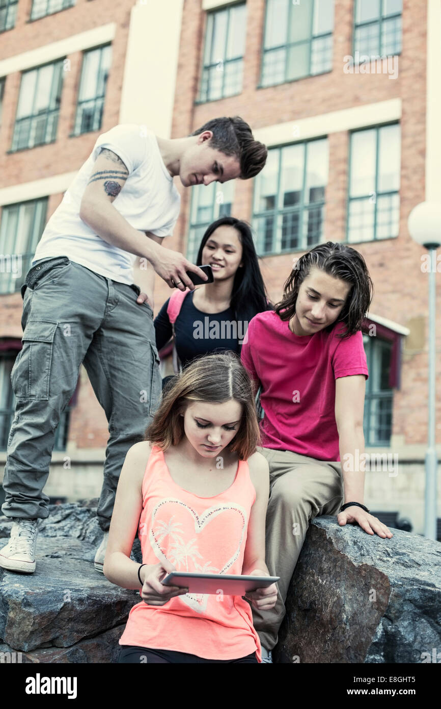 High school students using technologies on rock at schoolyard - Stock Image