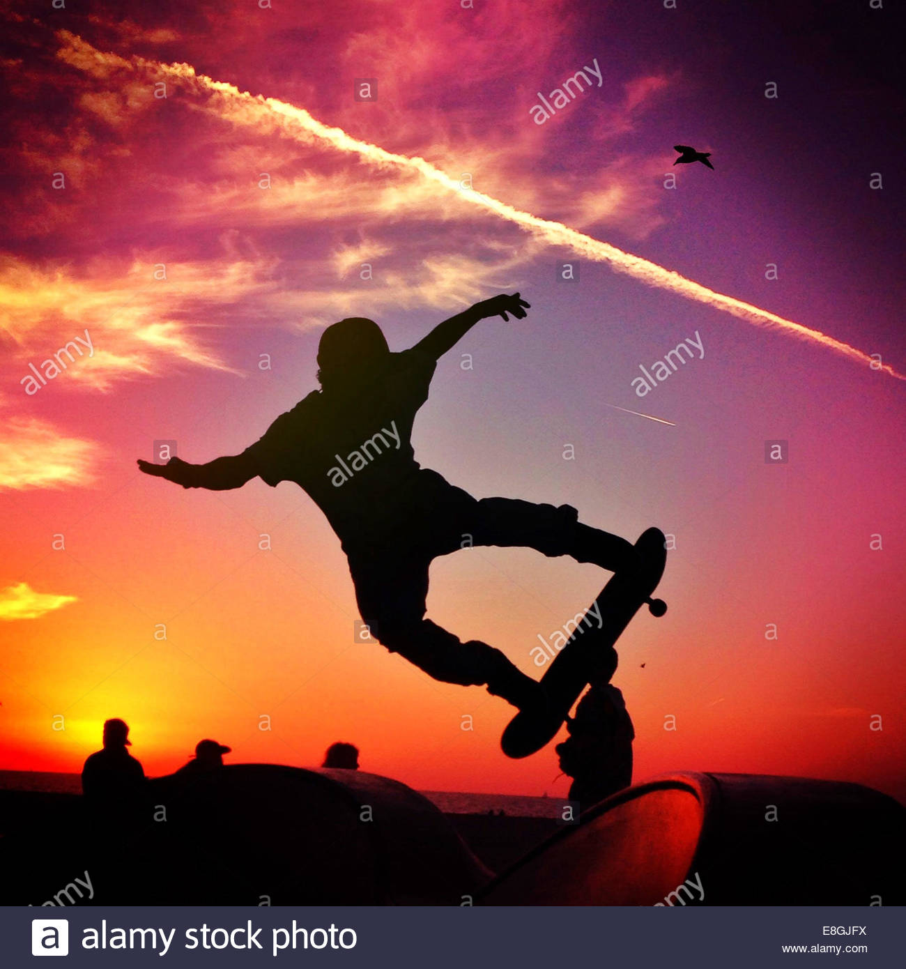 Silhouette of man Skateboarding at sunset - Stock Image
